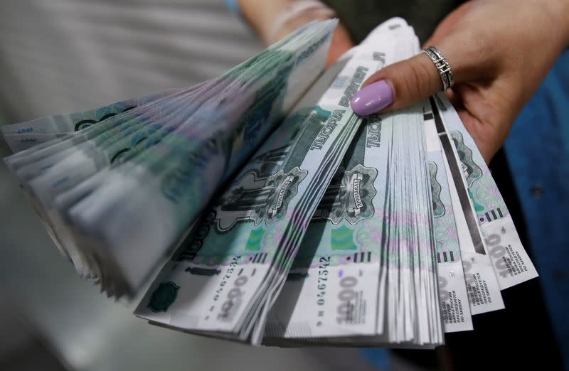 An employee holds 1000 Russian Roubles notes at Goznak printing factory in Moscow