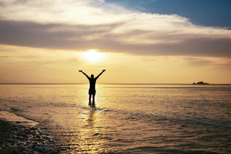 Rear view of happy man with arms outstretched standing in sea at amazing sunset.
