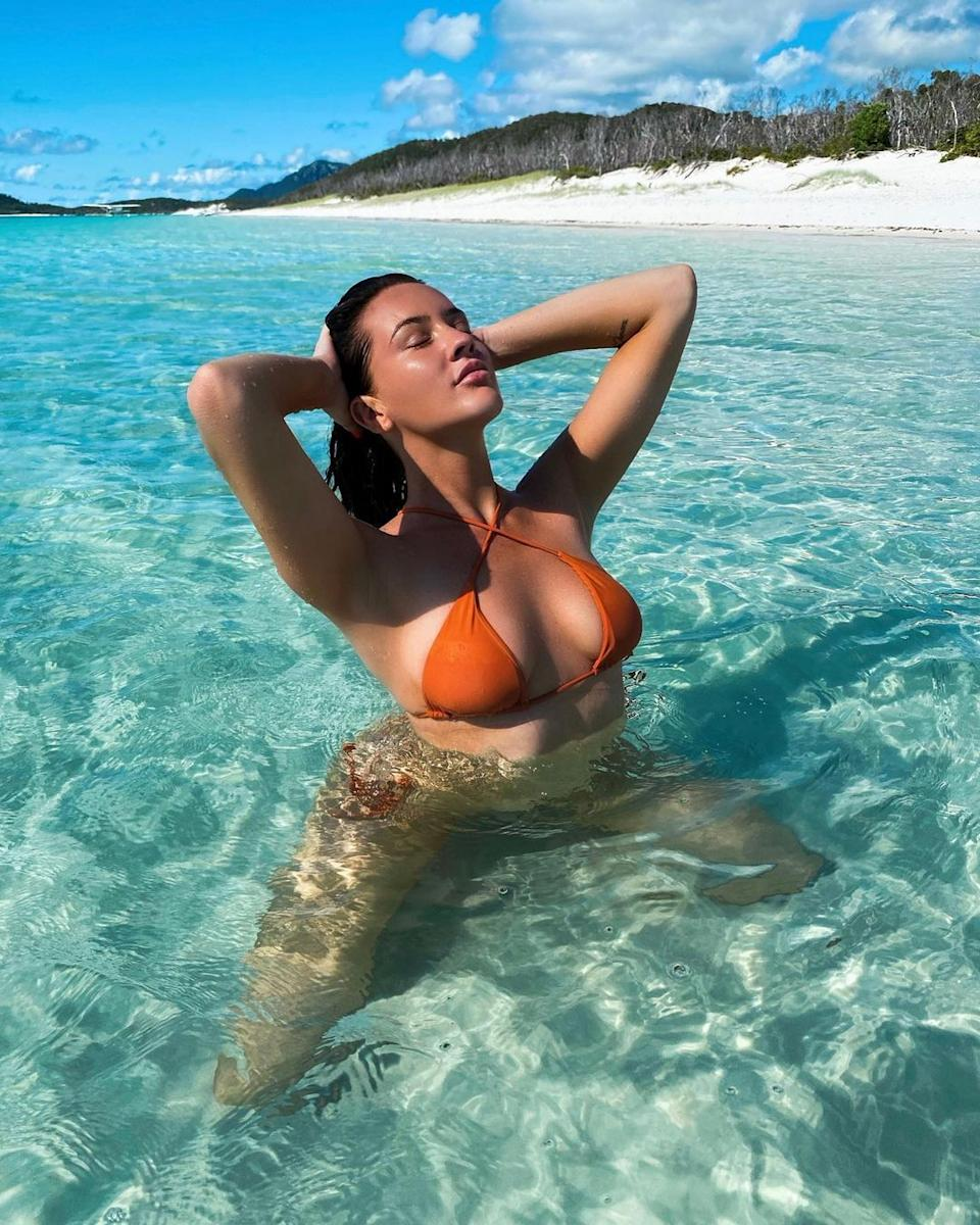 Ines Basic in an orange upside down bikini