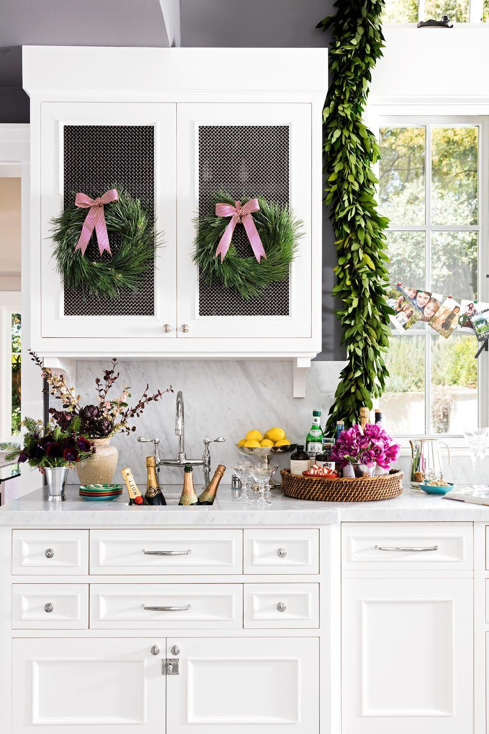<p>Though the lush garland framing the window adds so much vibrancy to this kitchen, it's the collection of family Christmas cards hanging across the window that brings personal character to the space and also shares the joy with neighbors. Hang some string across the window and add the cards as they come.</p>