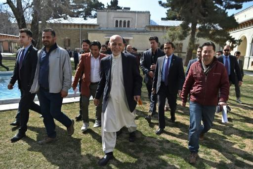 Afghan President Ashraf Ghani (C), walking with journalists after a press conference at the presidential palace, said he would not commit to a clause in the US-Taliban deal calling for a massive prisoner exchange