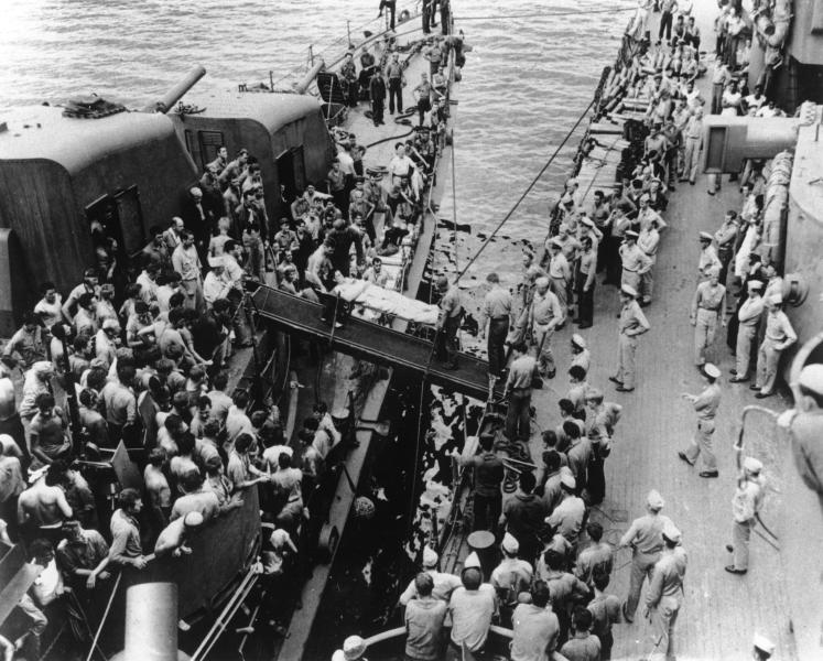 FILE - In this Aug. 14, 1943 file photo, a survivor of the USS Helena is transferred on a gangplank from the rescuing destroyer, left, to a U.S. battleship. Nearly 75 years after the USS Helena was sunk by Japanese torpedoes in the waters off the Solomon Islands in the South Pacific, an expedition backed by Microsoft co-founder Paul Allen reported finding its wreckage. The March 23, 2018 discovery revives stories of the battle-tested ship's endurance and the nearly unbelievable survival story of 165 of the crewmen. In all, 732 of the 900 crew survived its July 5, 1943 sinking. (AP Photo/File)