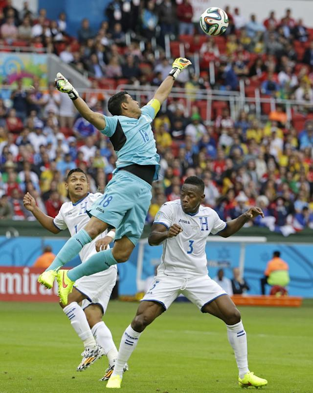 Honduras' goalkeeper Noel Valladares leaps past his teammates Emilio Izaguirre and Maynor Figueroa (3) to punch the ball away during the group E World Cup soccer match between France and Honduras at the Estadio Beira-Rio in Porto Alegre, Brazil, Sunday, June 15, 2014. (AP Photo/Fernando Vergara)