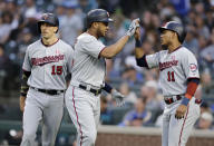 Minnesota Twins' Jonathan Schoop is greeted at home by Jorge Polanco, right, and Jason Castro, left, after hitting a three-run home run off Seattle Mariners' Parker Markel during the third inning of a baseball game Saturday, May 18, 2019, in Seattle. (AP Photo/John Froschauer)