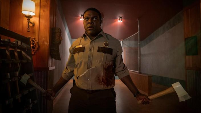 Sam Richardson, dressed as a park ranger, wields a hatchet and a large axe.