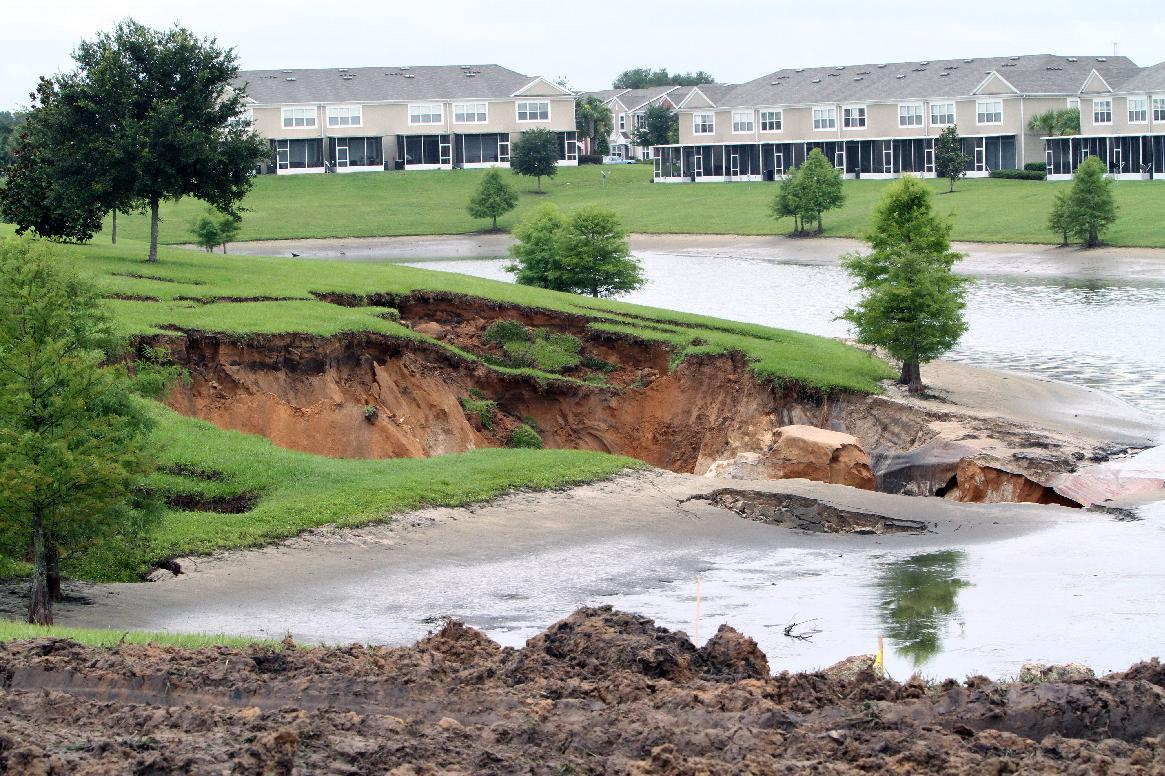A large sinkhole opened between apartments at the Fore Ranch subdivision in Ocala, Fla., Monday, June 25, 2012. Tropical Storm Debby raked the Tampa Bay area with high wind and heavy rain Monday in a drenching that could top 2 feet over the next few days and trigger widespread flooding. (AP Photo/The Ocala Star-Banner, Bruce Ackerman)