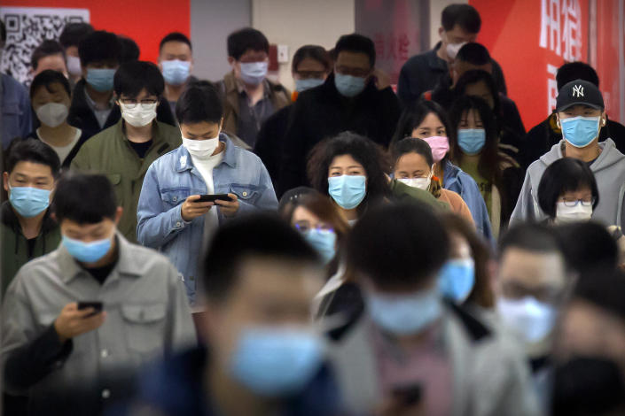 Image: Commuters wear face masks to protect against the spread of new coronavirus as they walk through a subway station in Beijing, (Mark Schiefelbein / AP)