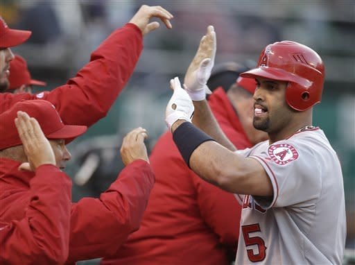 Los Angeles Angels' Albert Pujols (5) is congratulated after hitting an RBI sacrifice fly off Oakland Athletics' Graham Godfrey in the first inning of a baseball game, Tuesday, May 22, 2012, in Oakland, Calif. (AP Photo/Ben Margot)