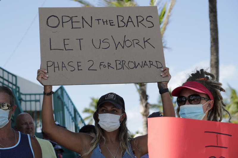 "People hold signs during a ""Right to Work"" rally outside of the Elbo Room bar , which remains closed, during the new coronavirus pandemic, Tuesday, June 16, 2020, in Fort Lauderdale, Fla. Across Florida, bars were part of the Phase 2 reopenings that occurred earlier in June, except in three counties in South Florida. (AP Photo/Lynne Sladky)"