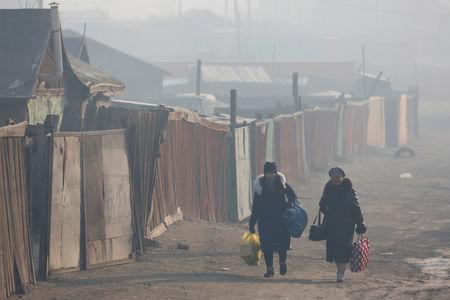 Women walk with their belongings amid smog in Sukhbaatar district of Ulaanbaatar, Mongolia January 31, 2019. Picture taken January 31, 2019. REUTERS/B. Rentsendorj