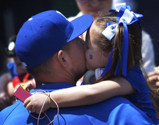 Kansas City Royals' Billy Butler gets a kiss from one of his daughters before the first of two baseball games against the Cleveland Indians, Sunday, April 28, 2013, in Kansas City, Mo. (AP Photo/Reed Hoffmann)