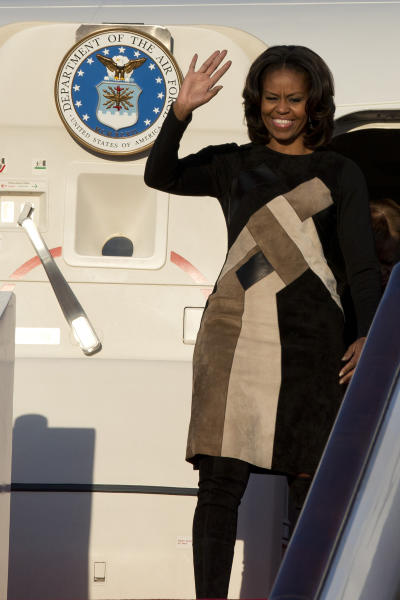 U.S. First Lady Michelle Obama waves as she arrives at Capital International Airport in Beijing, China, Thursday, March 20, 2014. Michelle Obama has arrived in Beijing with her mother and daughters to kick off a seven-day, three-city tour where she will focus on education and cultural exchange. (AP Photo/Alexander F. Yuan, Pool)