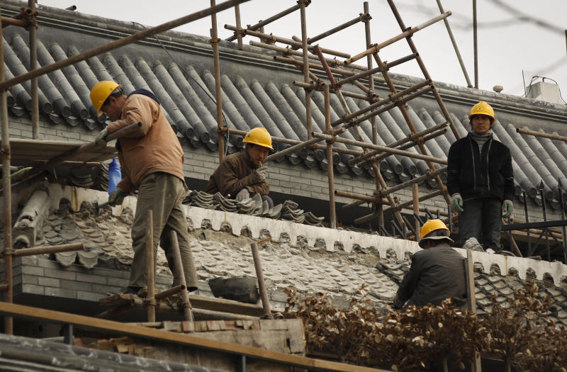 In this photo taken Thursday, March 22, 2012, Chinese workers fix the tiled roof of a traditional house at Hou Hai in Beijing, China, Thursday, April 12, 2012. The World Bank cut its growth forecast for China on Thursday, adding to warnings the world's second-largest economy might slow too abruptly, and said Beijing should be ready to launch a new stimulus if needed. (AP Photo/Vincent Thian)
