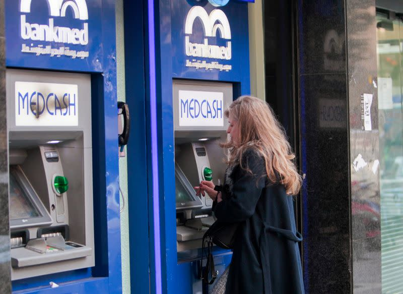 A woman uses an automated teller machine (ATM) of Bankmed in Beirut