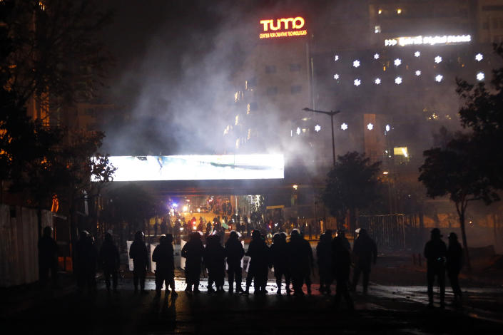 Lebanese riot police fire tear gas towards supporters of the Shiite Hezbollah and Amal groups in Beirut, Lebanon, Tuesday, Dec. 17, 2019. Supporters of Lebanon's two main Shiite groups Hezbollah and Amal have clashed with security forces and set fire to cars in Beirut in a third consecutive night of violence in the capital. The unrest early Tuesday apparently was triggered by a video circulating online that shows a man insulting Shiite and religious figures. (AP Photo/Bilal Hussein)