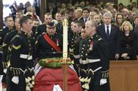 Canadian Prime Minister Stephen Harper and his wife Laureen (R) rise as the coffin of Cpl. Nathan Cirillo is carried by pallbearers at his regimental funeral service in Hamilton, Ontario October 28, 2014. Cirillo was standing guard at the National War Memorial in Ottawa last Wednesday when he was killed by a gunman who went on to open fire on Parliament Hill. REUTERS/Nathan Denette/Pool (CANADA - Tags: POLITICS MILITARY CRIME LAW OBITUARY)