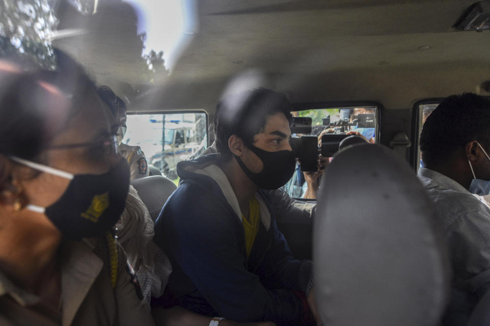 Bollywood actor Shah Rukh Khan's son Aryan Khan, center, escorted by law enforcement officials sits inside a vehicle outside the Narcotics Control Bureau (NCB) to appear before a court in Mumbai, India, Monday, Oct.4, 2021. (AP Photo)