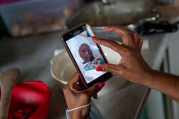 PHOTO: Menge Mokwatle shares a photograph of her late husband Benedict Sami Vilakazi, who died of COVID-19, during an Ukugeza cleansing ceremony at Vilakazi's home in Soweto, South Africa, Nov. 21, 2020. (Jerome Delay/AP)
