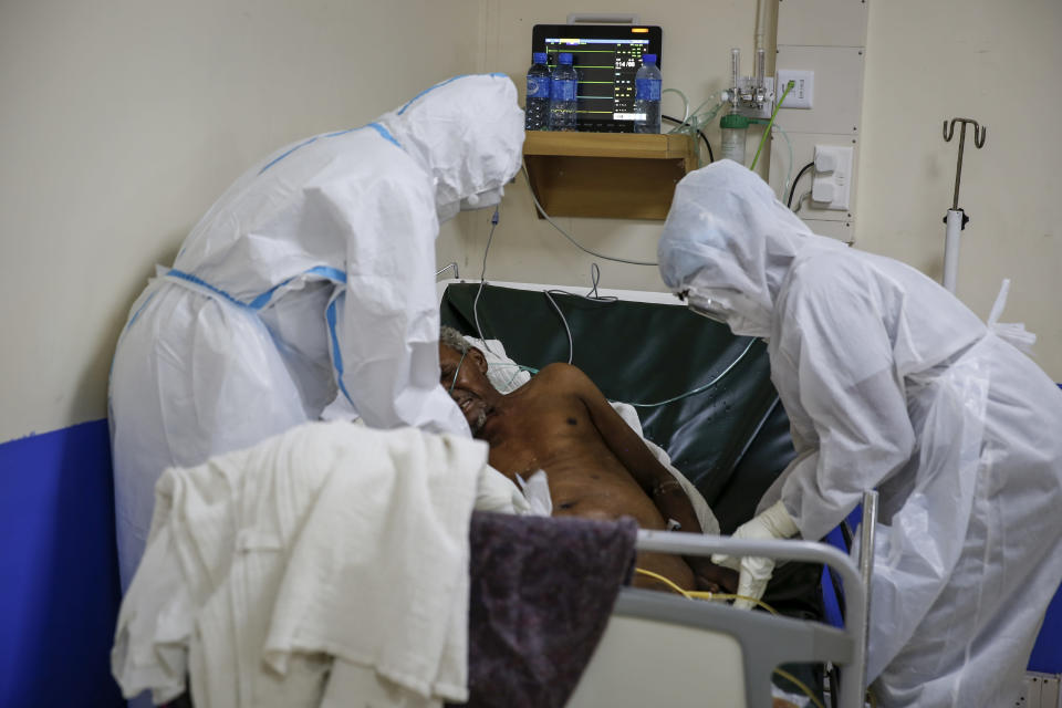 Medical workers attend to a coronavirus patient in the intensive care unit of an isolation and treatment center for those with COVID-19 in Machakos, south of the capital Nairobi, in Kenya Tuesday, Nov. 3, 2020. As Africa is poised to surpass 2 million confirmed coronavirus cases it is Kenya's turn to worry the continent with a second surge in infections well under way. (AP Photo/Brian Inganga)