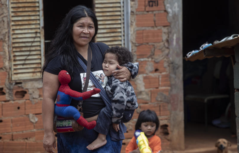 A Guarani Mbya woman with her son and his Spiderman doll walks outside, on her indigenous community's property in Sao Paulo, Brazil, Friday, Jan. 31, 2020. Members of the tribe, living in the smallest demarcated indigenous land of Brazil, were surprised by workers with chainsaws who were making way for a five-building apartment complex in a nearby forested area. They say they weren't consulted, as the law states, but the company has permits to build. The tension between a builder with projects in nine Brazilian states and a 40-family indigenous community is a microcosm of what's playing out elsewhere in the country. (AP Photo/Andre Penner)