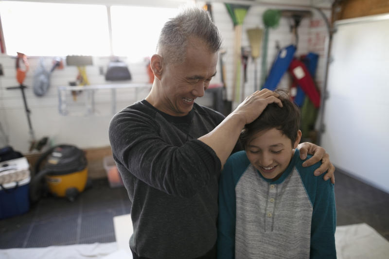 Playful father ruffling sons hair in garage