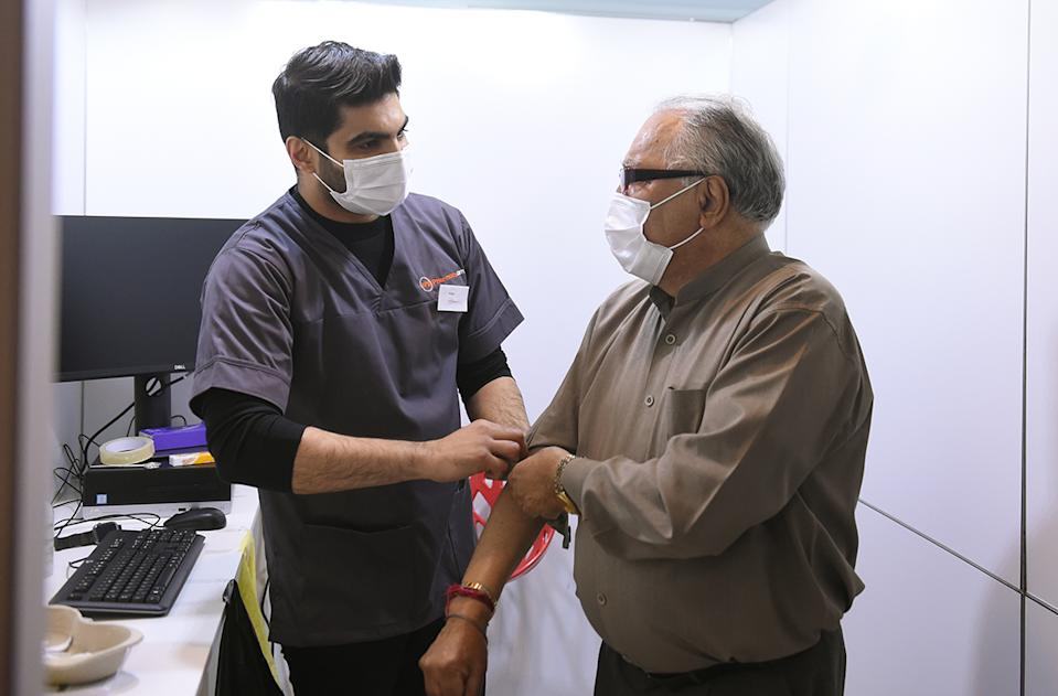 Aneet Kapoor, a pharmacist from Manchester, got to vaccinate his 79-year-old dad, Suneel, who has been shielding during lockdown (MCC)