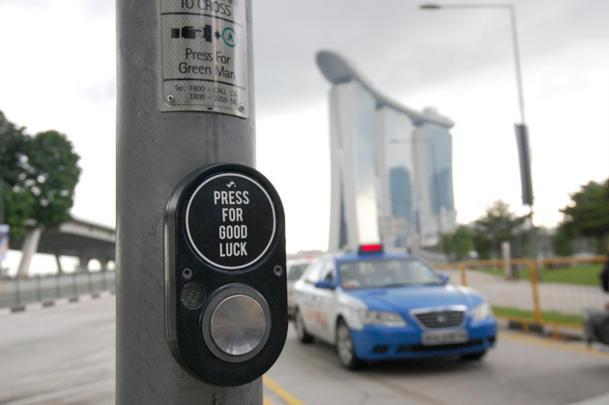Lo's work, such as this sticker pasted at a traffic light near Marina Bay Sands, was posted online and went viral. (Photo credit: Samantha Lo collection)