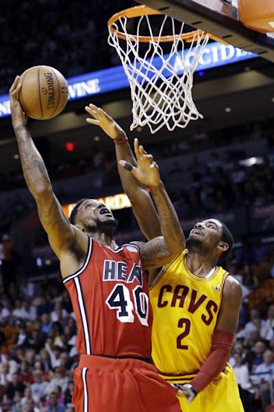 Miami Heat forward Udonis Haslem (40) shoots against Cleveland Cavaliers guard Kyrie Irving (2) during the first half of an NBA basketball game, Sunday, Feb. 24, 2013, in Miami. (AP Photo/Wilfredo Lee)