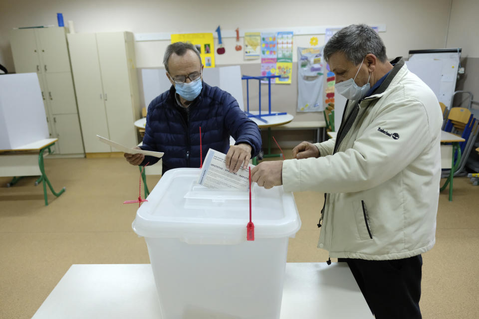 A man casts his ballot for the local elections at a polling station in Mostar, Bosnia, Sunday, Dec. 20, 2020. Divided between Muslim Bosniaks and Catholic Croats, who fought fiercely for control over the city during the 1990s conflict, Mostar has not held a local poll since 2008, when Bosnia's constitutional court declared its election rules to be discriminatory and ordered that they be changed. (AP Photo/Kemal Softic)