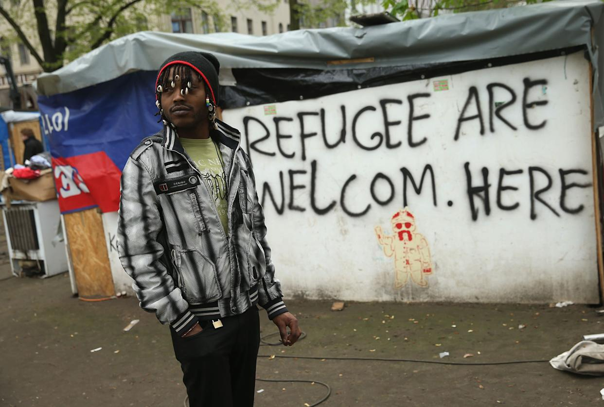 BERLIN, GERMANY - APRIL 08: A refugee from Niger stands by near huts that were being torn down at a temporary, city-tolerated refugee camp at Oranienplatz in Kreuzberg district on April 8, 2014 in Berlin, Germany. Refugees, many of them from Africa who came to Germany via Lampedusa, began dismantling their shelters today after many of them agreed to a deal with city authorities to move to a renovated hostel. Not all of the several hundred refugees, some of whom have been living at the Oranienplatz camp almost a year, have agreed to the deal, and while some said they will go elsewhere, some insist they will stay, despite a city order to vacate. (Photo by Sean Gallup/Getty Images)