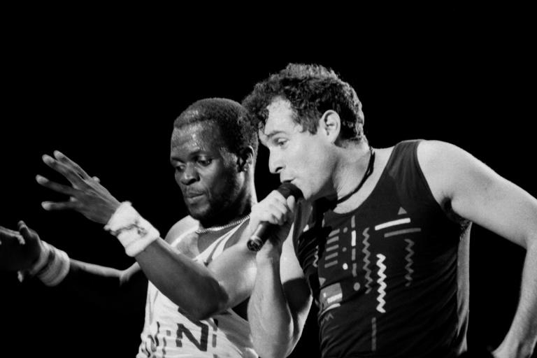 Johnny Clegg (R) performed in the band Savuka for years under apartheid until group member Dudu Zulu (L) was shot dead in 1992 and dancer Dudu Zulu of South African band Savuka perform on stage at the Amnesty International Concert on October 10, 1988 in Abidjan. (AFP Photo/-)