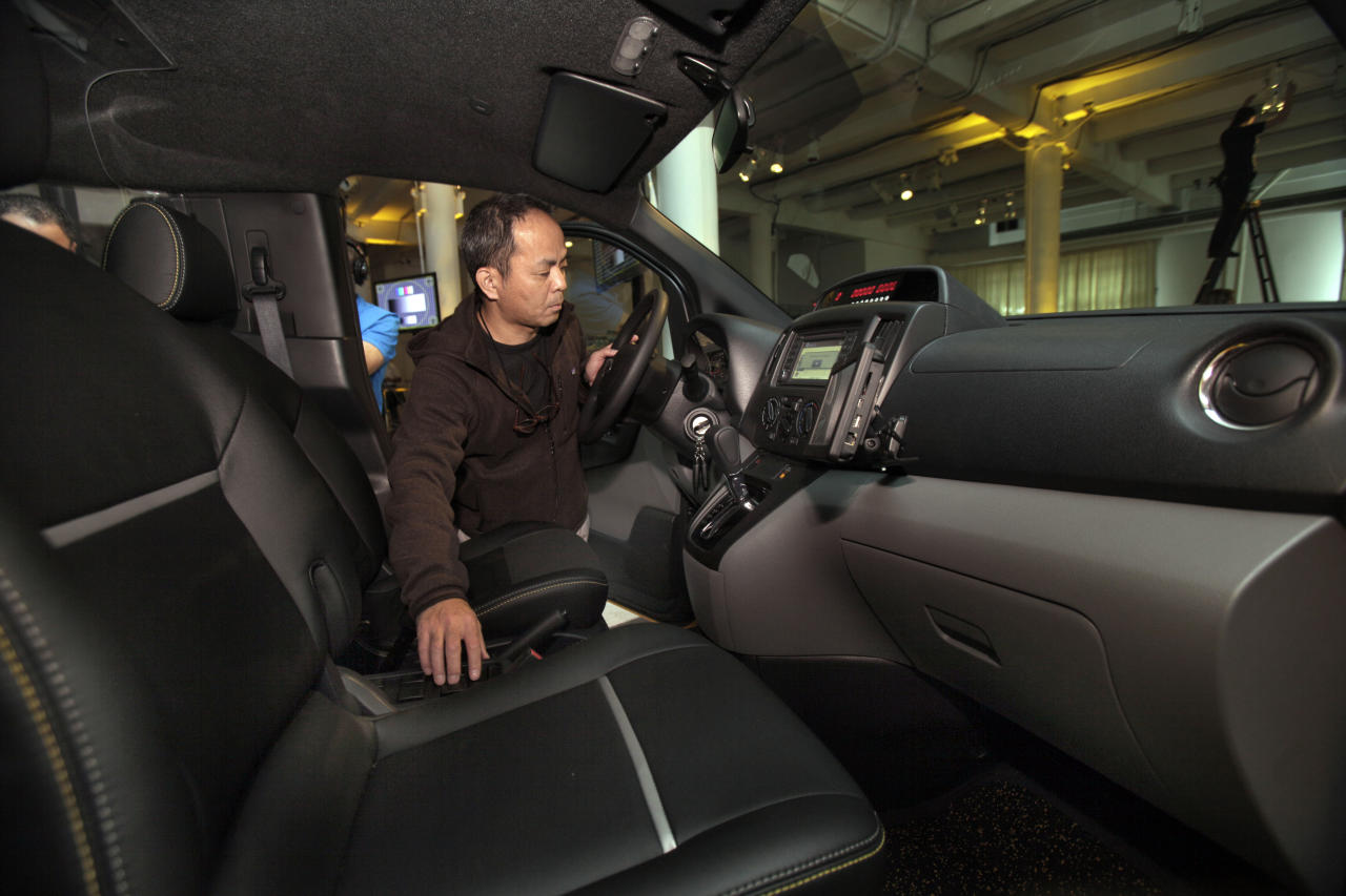 Nissan Model Relations Manager Kengo Yoneda tests the instrument panel in the driver's compartment of the prototype of a Nissan NV 200 New York City taxi, in New York, Monday, April 2, 2012. The iconic New York City taxi has gotten a passenger-friendly makeover from Nissan with low-annoyance horns, USB chargers and germ-fighting seats to cut down on bad odors. Medallion owners will be required to buy the Nissan NV 200 at a cost of about $29,000 starting in late 2013. (AP Photo/Richard Drew)