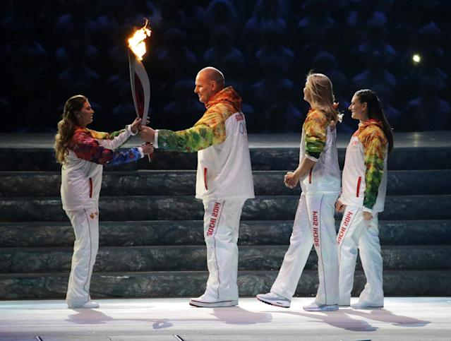Russian wrestler Alexander Karelin, second from left, hands the torch to Russian gymnast Alina Kabaeva, left, as Russian tennis player Maria Sharapova, second from right, and Russian pole vaulter Yelena Isinbayeva look on during the opening ceremony of the 2014 Winter Olympics in Sochi, Russia, Friday, Feb. 7, 2014