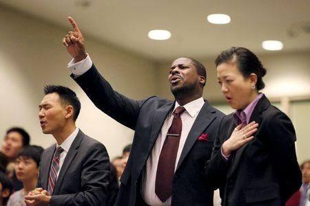 Rev. Jason Noh (L), Pastor Q. Wilson (C) and Rev. Lisa Pak pray for Canadian pastor Hyeon Soo Lim who is being held in North Korea during a joint multi-cultural prayer meeting at Light Korean Presbyterian Church in Toronto, December 20, 2015.  REUTERS/Hyungwon Kang