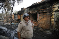A fire fighting officer stands at the Gokul Puri tyre market which was burnt in Tuesday's violence in New Delhi, India, Wednesday, Feb. 26, 2020. At least 20 people were killed in three days of clashes in New Delhi, with the death toll expected to rise as hospitals were overflowed with dozens of injured people, authorities said Wednesday. The clashes between Hindu mobs and Muslims protesting a contentious new citizenship law that fast-tracks naturalization for foreign-born religious minorities of all major faiths in South Asia except Islam escalated Tuesday. (AP Photo/Altaf Qadri)