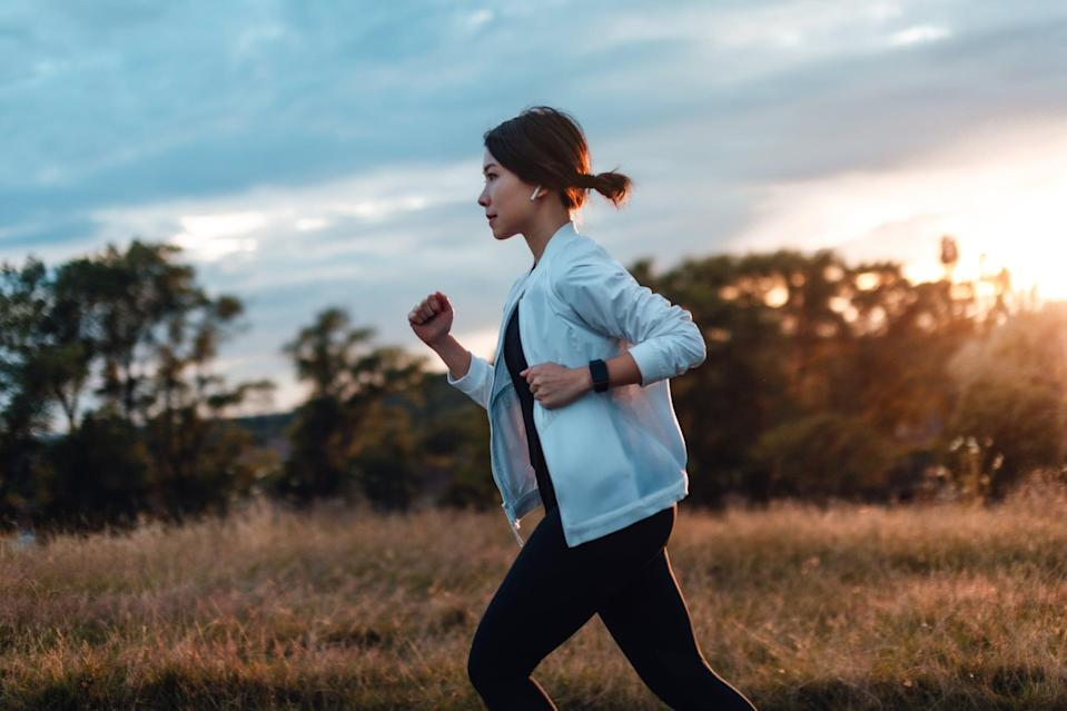 Side view of determined young Asian woman listening to music with earphones, jogging at the park, against sunset.