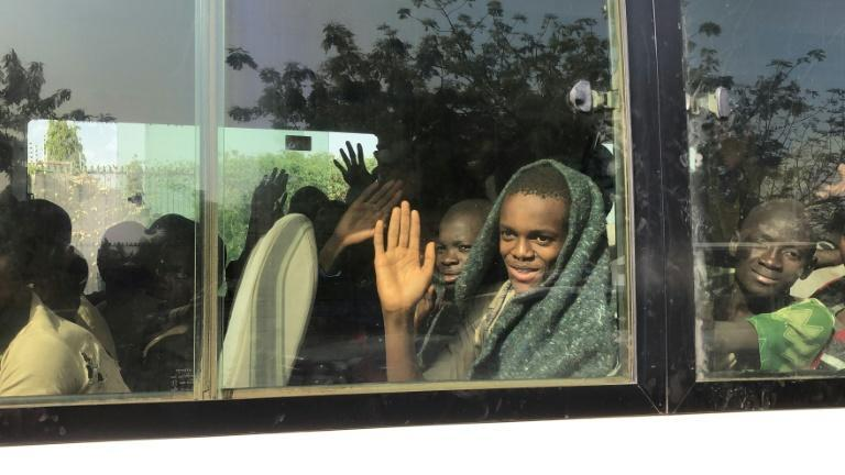 Happy to be free: A schoolboy waves from a bus after the end of his ordeal