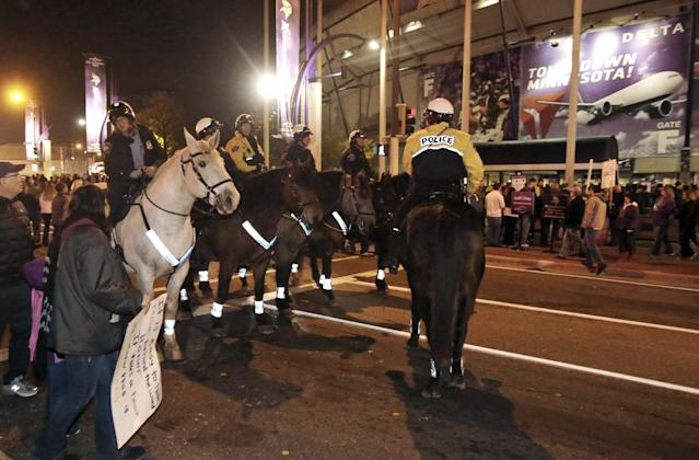 Minneapolis police on horseback stand by outside the Metrodome as several hundred American Indians and their supporters gather to protest the Washington Redskins' name, prior to the Redskins' NFL football game against the Minnesota Vikings, Thursday, Nov. 7, 2013, in Minneapolis. (AP Photo/Jim Mone)
