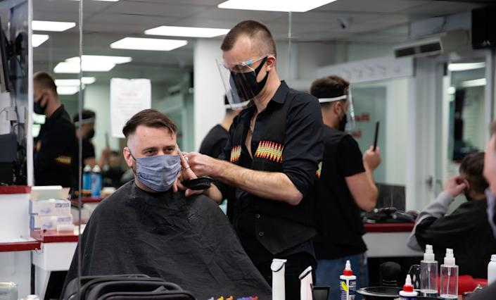 A hairdresser wearing a face mask and shield cuts hair of a client during the reopening. Shops, restaurants, bars and other businesses reopened today after almost four months as further lockdown rules are relaxed in England. (Photo by Yunus Dalgic / SOPA Images/Sipa USA)
