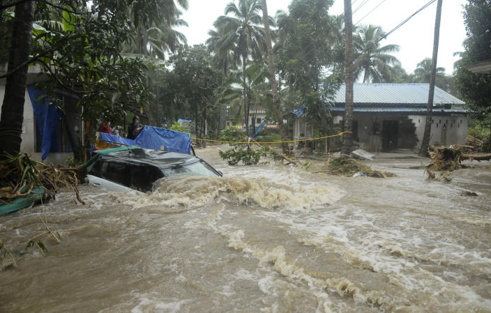 A car is submerged as roads and houses are engulfed in water following heavy rain and landslide in Kozhikode, Kerala state, India, Thursday, Aug. 9, 2018. Landslides triggered by heavy monsoon rains have killed more than a dozen people in southern India, cutting off road links and submerging several villages. (AP Photo)