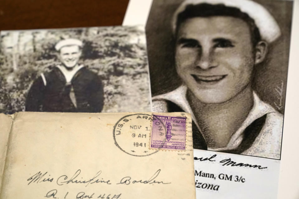 Photos of sailor William Edward Mann and a letter written from him and post-marked from the USS Arizona, where he died during the bombing of Pearl Harbor, are displayed at the home of his niece, Teri Mann Whyatt, Wednesday, July 14, 2021, in Newcastle, Wash. In recent years, the U.S. military has taken advantage of advances in DNA technology to identify the remains of hundreds of sailors and Marines who died in the 1941 bombing of Pearl Harbor and has sent them home to their families across the country for burial. The remains of 85 unknowns from the USS Arizona, which lost more men during the attack than any other ship, haven't received this treatment, however. (AP Photo/Elaine Thompson)