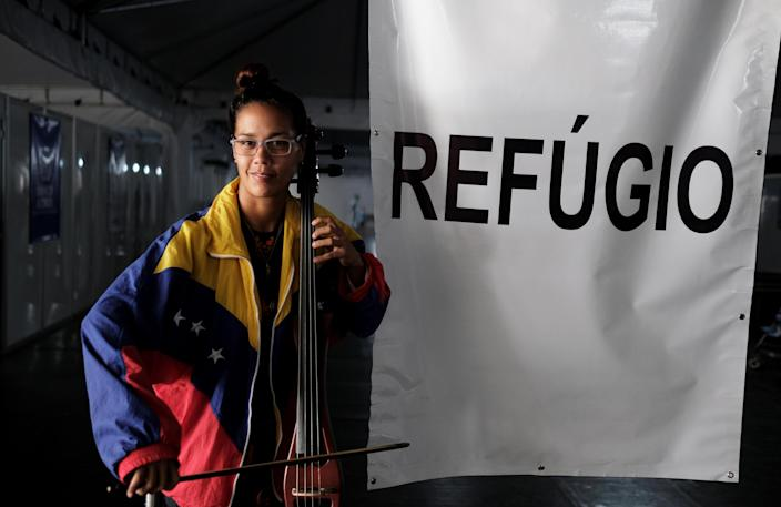 <p>Dulce from Venezuela poses with her instrument after she obtained a refugee status, through the Federal Police and the United Nations High Commissioner for Refugees (UNHCR) at the Pacaraima border control, Roraima state, Brazil, Aug. 9, 2018. (Photo: Nacho Doce/Reuters) </p>