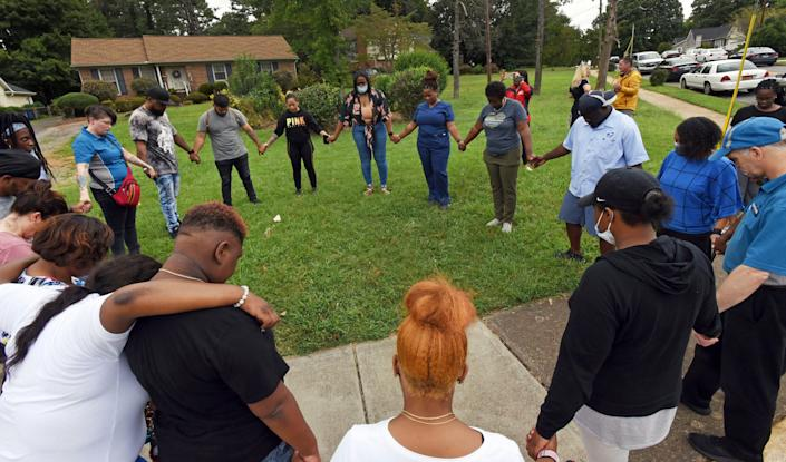 Parents gather in prayer at the corner of Petree and Polo roads after a shooting at Mount Tabor High School in Winston-Salem, N.C., that left one student dead, Wednesday, Sept. 1, 2021.
