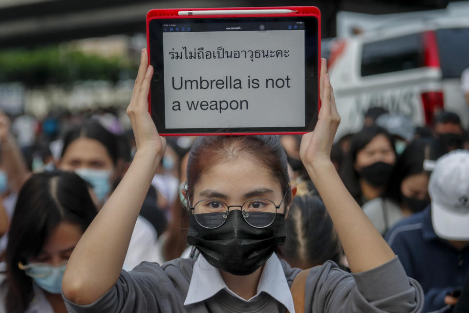 A young pro-democracy activist displays a message during a demonstration at Kaset intersection, suburbs of Bangkok, Thailand, Monday, Oct. 19, 2020. Thai authorities worked Monday to stem a growing tide of protests calling for the prime minister to resign by threatening to censor news coverage, raiding a publishing house and attempting to block the Telegram messaging app used by demonstrators. (AP Photo/Sakchai Lalit)