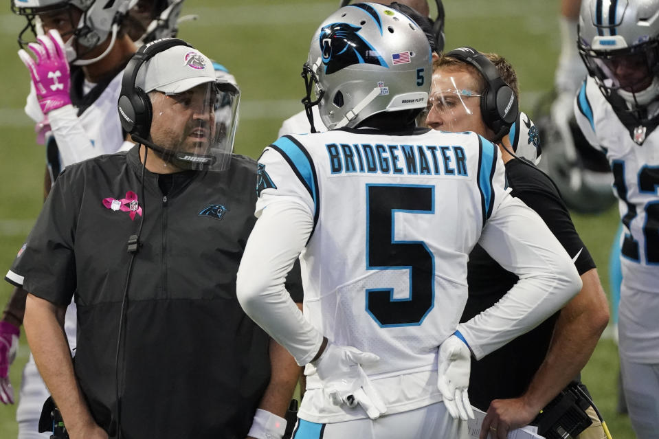 Carolina Panthers quarterback Teddy Bridgewater (5) speaks with Carolina Panthers head coach Matt Rhule during the second half of an NFL football game against the Atlanta Falcons, Sunday, Oct. 11, 2020, in Atlanta. (AP Photo/John Bazemore)