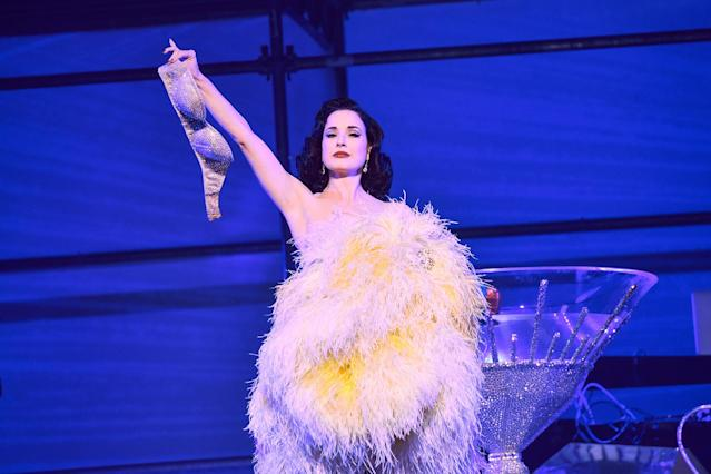 Dita Von Teese performs her signature striptease at the Philipp Plein show. (Photo: Getty Images)