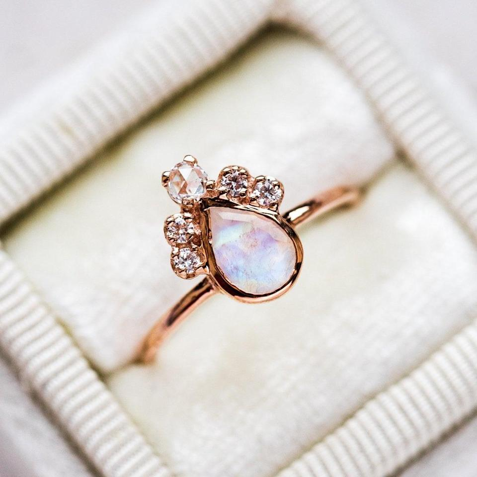 """<p>The cluster of diamonds that sit on top of the teardrop moonstone give the <a href=""""https://www.popsugar.com/buy/Pear-Moonstone-Crown-Ring-Rose-Gold-531205?p_name=Pear%20Moonstone%20Crown%20Ring%20in%20Rose%20Gold&retailer=localeclectic.com&pid=531205&price=595&evar1=fab%3Aus&evar9=44555978&evar98=https%3A%2F%2Fwww.popsugar.com%2Fphoto-gallery%2F44555978%2Fimage%2F47011754%2FPear-Moonstone-Crown-Ring-in-Rose-Gold&list1=wedding%2Cjewelry%2Crose%20gold%2Cengagement%20rings&prop13=api&pdata=1"""" rel=""""nofollow noopener"""" class=""""link rapid-noclick-resp"""" target=""""_blank"""" data-ylk=""""slk:Pear Moonstone Crown Ring in Rose Gold"""">Pear Moonstone Crown Ring in Rose Gold</a> ($595) so much pizazz. </p>"""