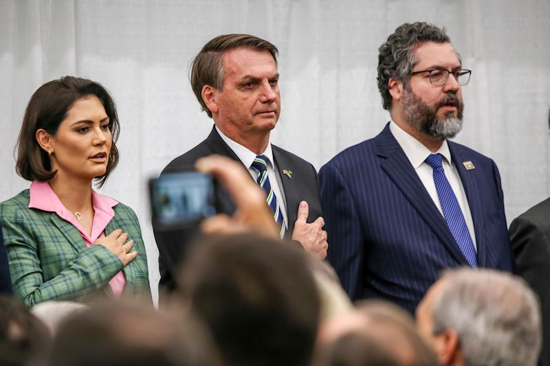Brazilian President Jair Bolsonaro (C), alongside Brazil's Minister of Foreign Affairs Ernesto Araujo (R), look on during the Brazilian national anthem in front of Miami's Brazilian community at Miami Dade College's Medical Campus in Miami, Florida, on March 9, 2020. (Photo by Zak BENNETT / AFP) (Photo by ZAK BENNETT/AFP via Getty Images)