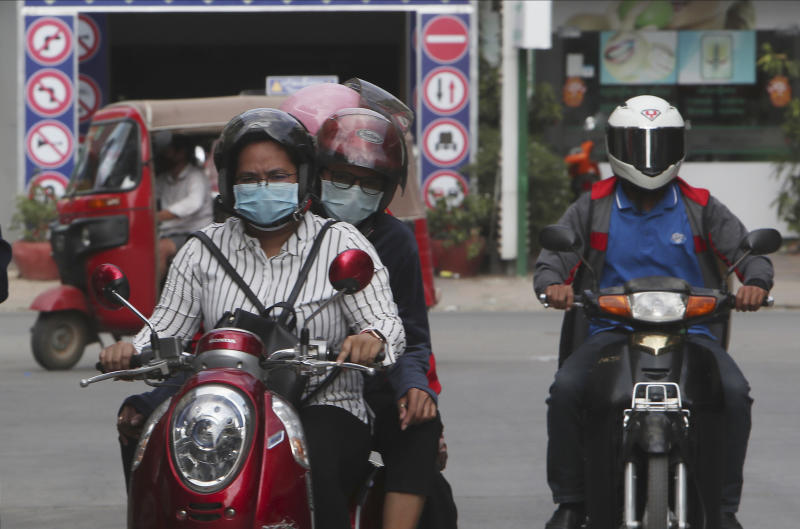 In this Friday, April 3, 2020, photo, motorists wear face masks to protect against the spread of the coronavirus in Phnom Penh, Cambodia. As governments across the world enact emergency measures to keep people at home and stave off the pandemic, some are unhappy about having their missteps publicized. Others are taking advantage of the crisis to silence critics and tighten control.(AP Photo/Heng Sinith)