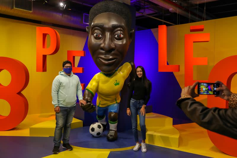 People pose for a picture near a sculpture of Brazilian soccer legend Pele at an exhibition marking his 80th birthday at the Soccer Museum in Sao Paulo